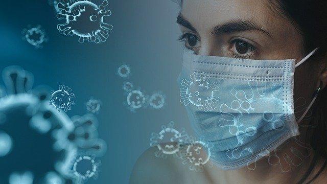 A képen egy szájmaszkot viselő fiatal női fej látható. A kép előterében a koronavírus látszik.