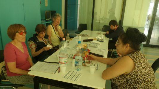 A klubtagok az asztal körül ülve beszélgetnek.