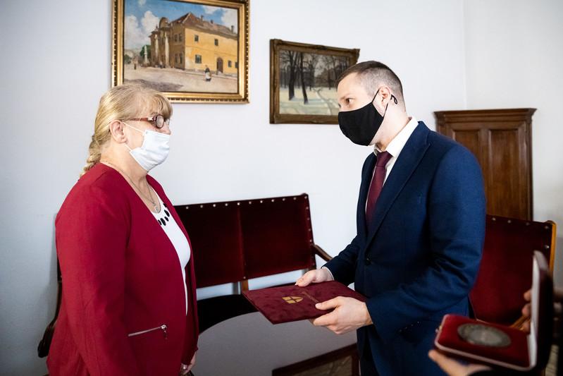 Soproni Tamás, Terézváros polgármestere átadja Erzsébetnek a kitüntetést: az érmet és az oklevelet.